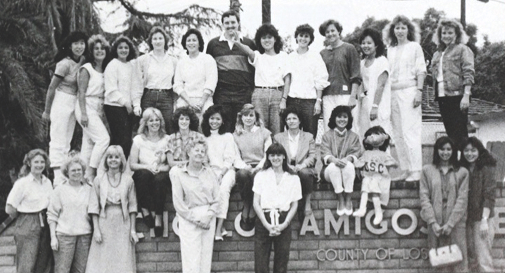Students and faculty surround the Rancho Los Amigos Hospital entrance sign for a photograph published in the 1987 edition of El Rodeo, USC's yearbook.