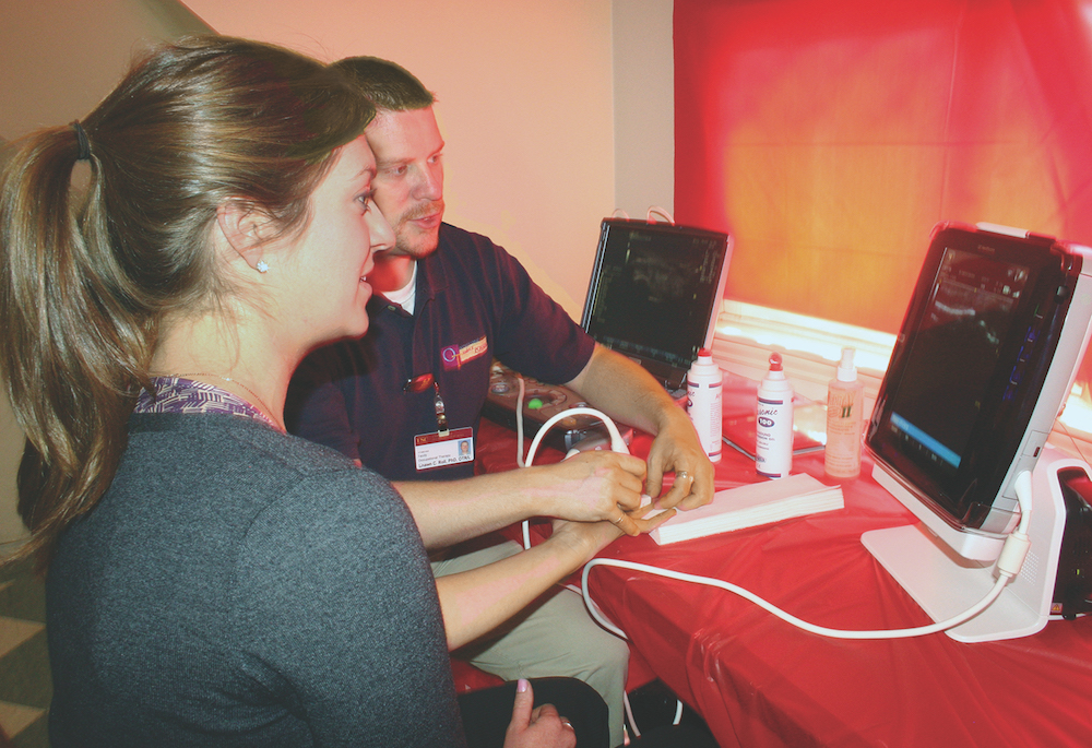 Occupational therapy graduate student Heather How (L) watches the monitor as division assistant professor Shawn Roll (R) demonstrates diagnostic ultrasonography. Photo by Chelsea Robinson