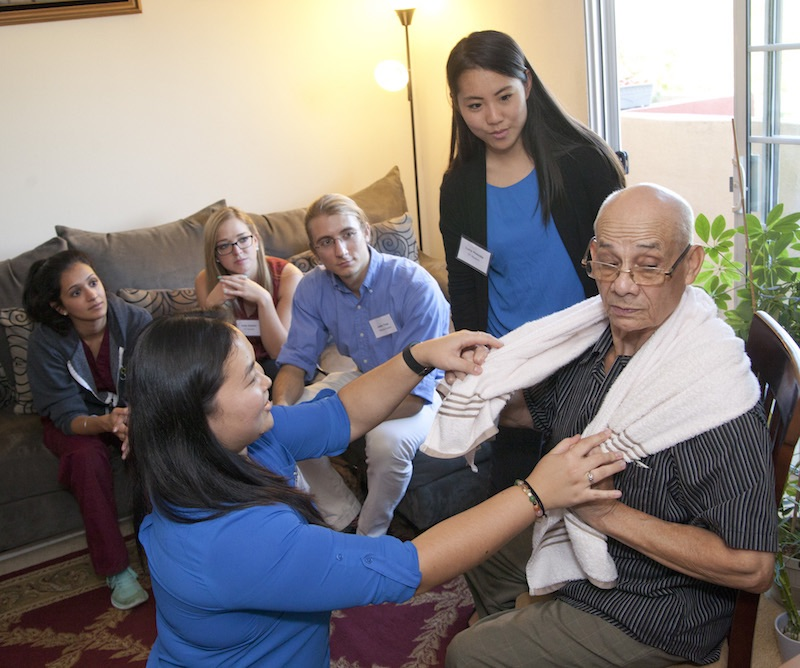 A group of health professions students, including USC Chan student Lucy Hosoda MA '16, OTD '17 (second from right), watch as Alyssa Kano DPT '17 teaches Leonel Aguirre a simple towel exercise to increase his tender neck's range of motion   Photo by John Skalicky