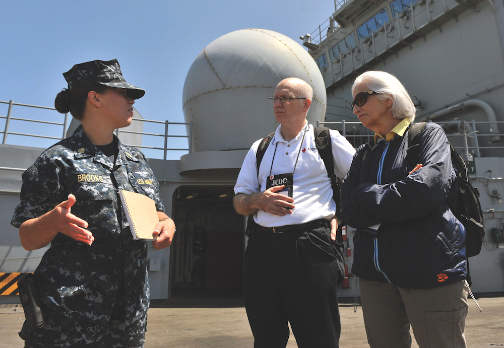 Florence Clark (right) listens with Roger Lowe (center), senior vice president of communications at the American Red Cross, as Chief Air Traffic Controller Gavrila Brooks (left) explains shipboard operations on the deck of the USS Makin Island amphibious assault ship during the Department of Defense's Joint Civilian Orientation Conference. Photo by Glenn Fawcett, U.S. Department of Defense