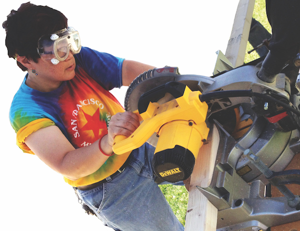 Donna Ozawa MA '15 works the miter saw to construct a wheelchair ramp