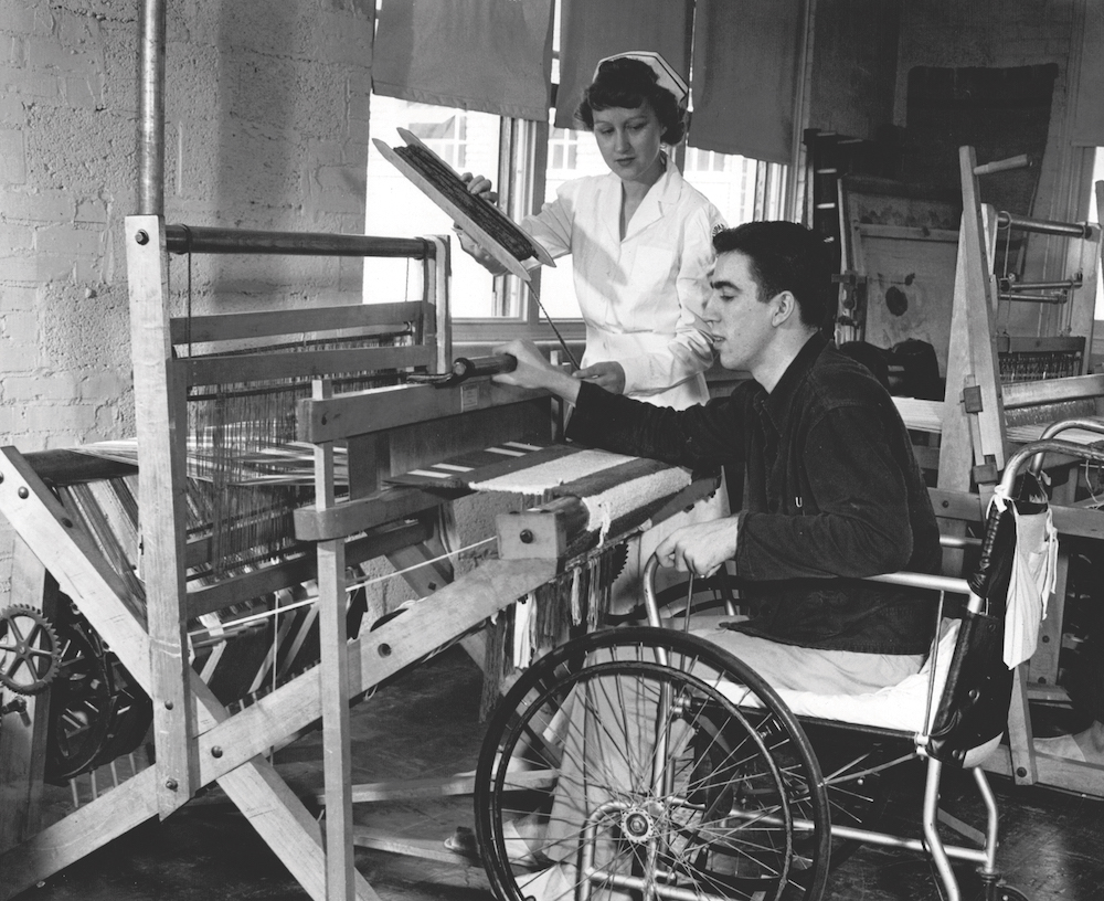 A young man works from his wheelchair at the weaving loom under the watchful eye of an unidentified therapist.