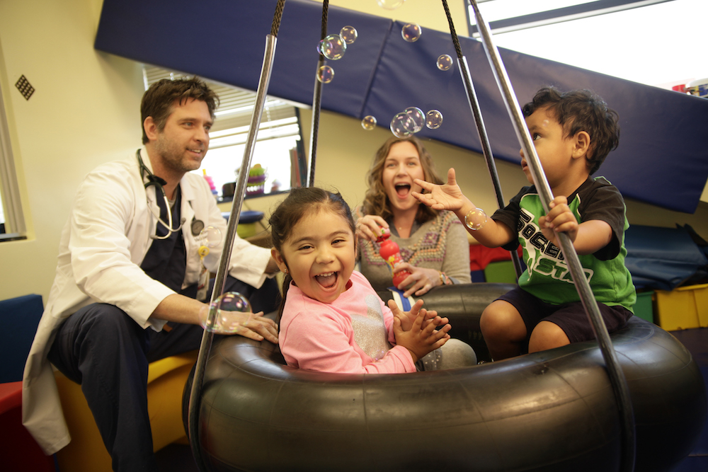 Dr. Jeff Egler, assistant professor of clinical family medicine, joins in the fun with Dr. Michelle Farmer during a group occupational therapy treatment session at USC-Eisner Pediatric and Family Medical Center. Photo by John Skalicky