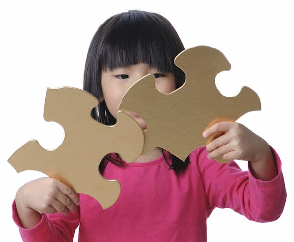 Girl with jigsaw puzzle pieces
