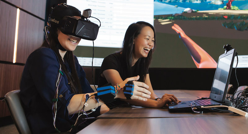Sook-Lei Liew, right, puts her REINVENT virtual reality rig through the paces | Photo by Nate Jensen