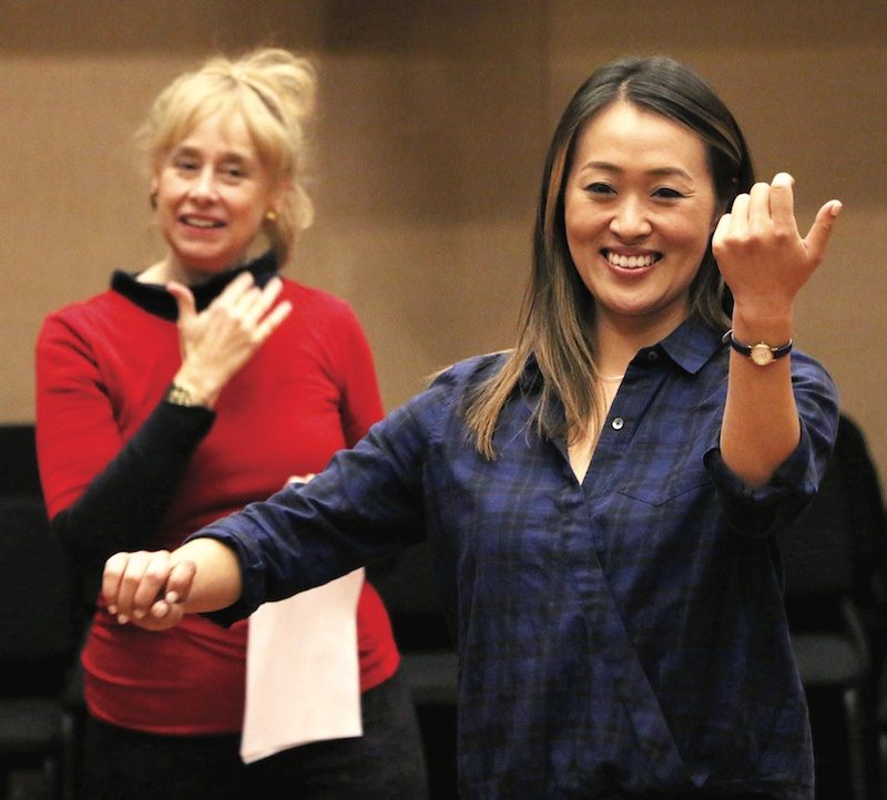 Annie Ting, right, simulates a violinist's playing posture while Janice Rocker watches | Photo by Erin Offenhauser