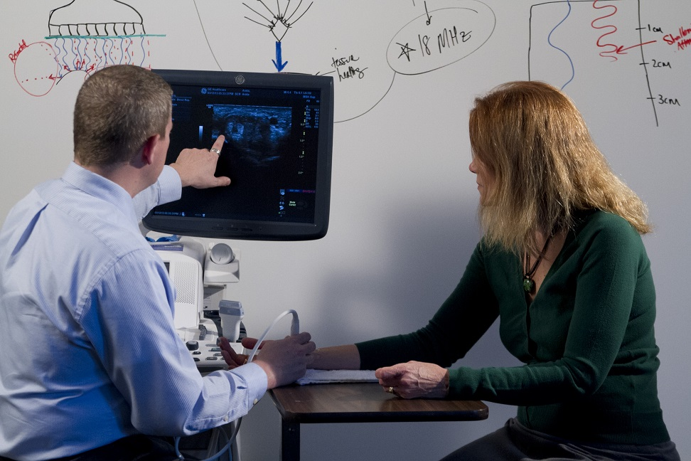 Dr. Roll using sonography to provide patient education and encourage movement of hand muscles as means of biofeedback