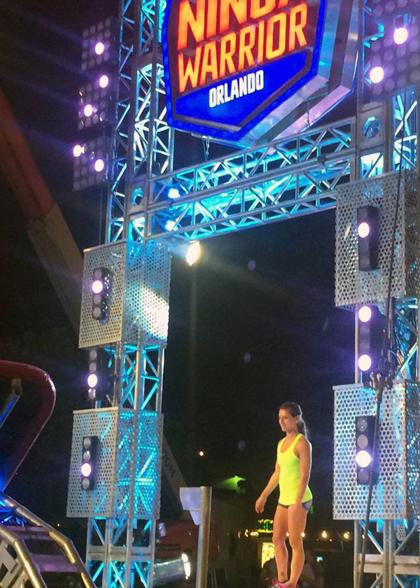 Alumna Karly Streisfeld '05 standing at the start of the American Ninja Warrior obstacle course
