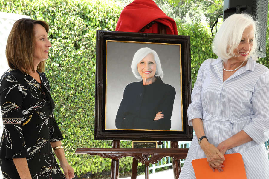 Grace Baranek and Florence Clark unveil the portrait honoring Clark's 42 years as a USC occupational therapy faculty member. (Photo by Glenn Marzano)