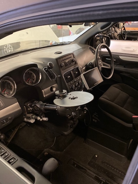Pictured is an adapted steering wheel to allow clients to drive in the horizontal plane instead of the usual vertical plane