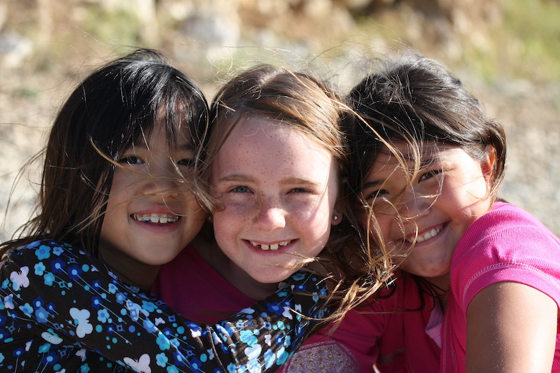 Three young girls smiling for a close up picture together