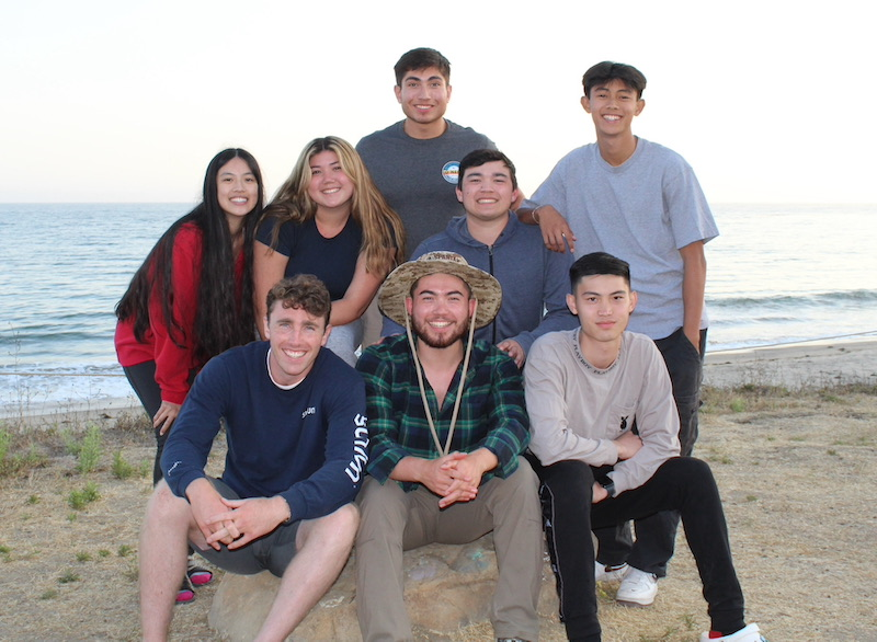 Eight young adults smiling for a picture at the beach