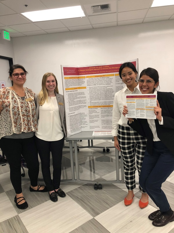 This image shows students presenting their program proposal poster