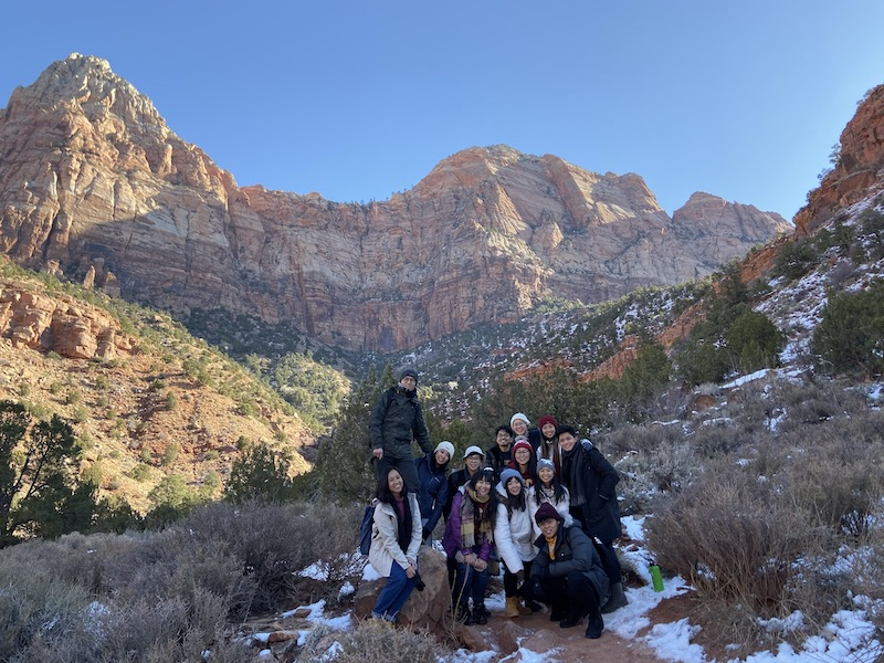 A group photo with the mountain on the background.