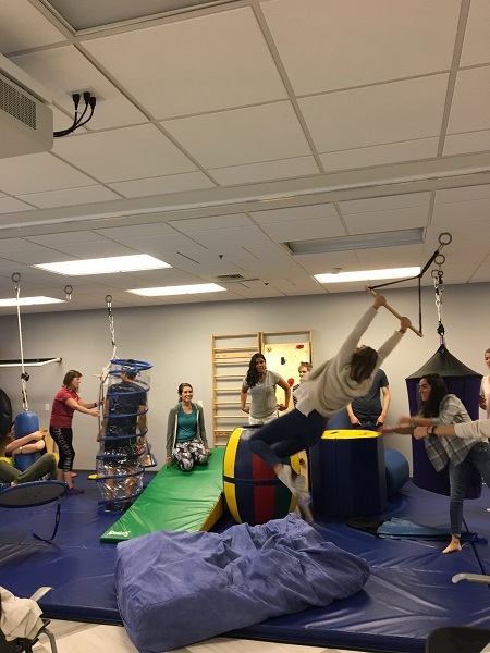 Photo of students using equipment in pediatric therapy gym