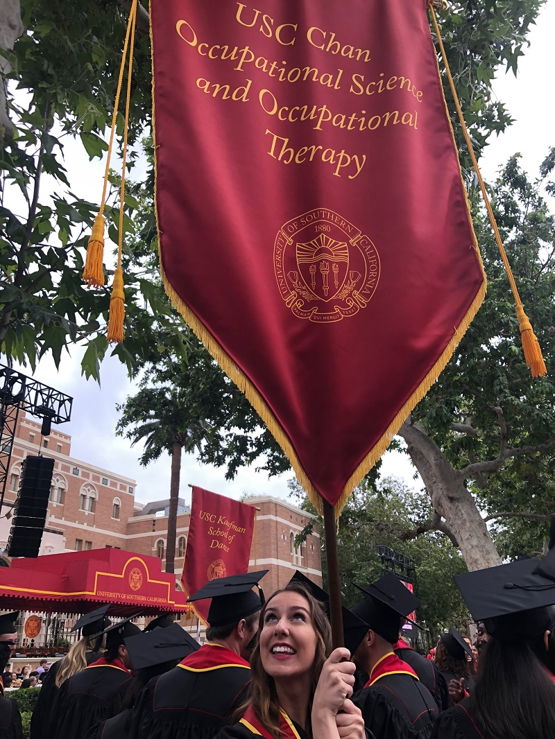 Me holding the banner at Commencement 2019