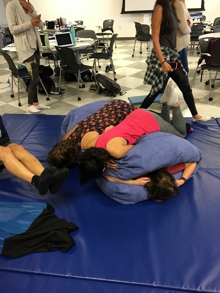 Photo of students providing deep pressure to another student