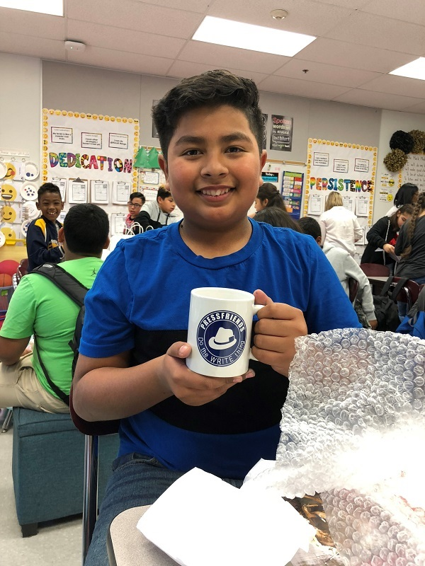 This image shows a student with a PressFriends mug