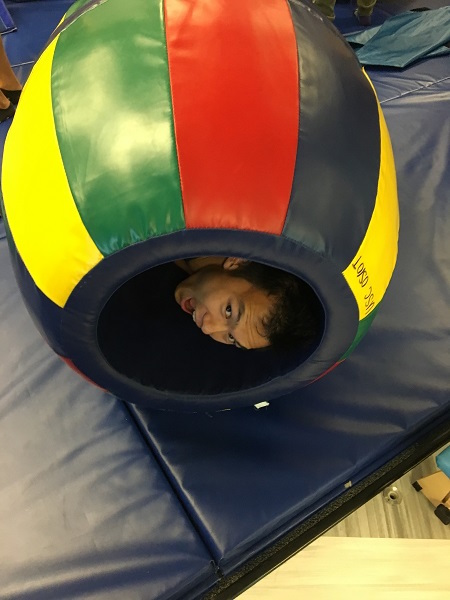 Photo of student rolling in equipment in SI therapy gym