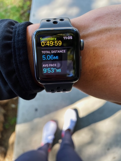 Pictured is an Apple Watch with the distance of 5 miles, pace 9 minutes and 53 seconds, and total run time 49 minutes and 59 seconds.